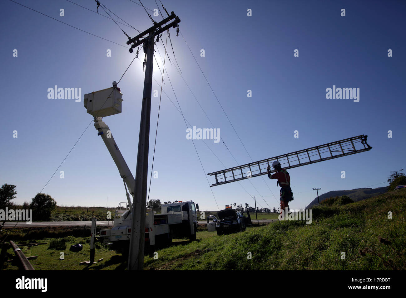 power company workers use a ladder and a cherry picker hoist replacing high voltage power cables - Stock Image