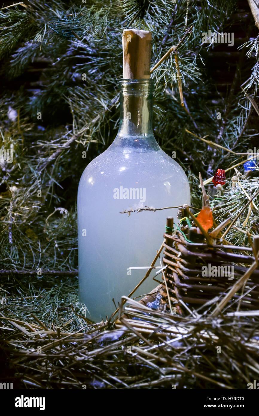 Holiday bottle of homemade strong drink vodka moonshine hooch near Christmas tree. Still life - Stock Image