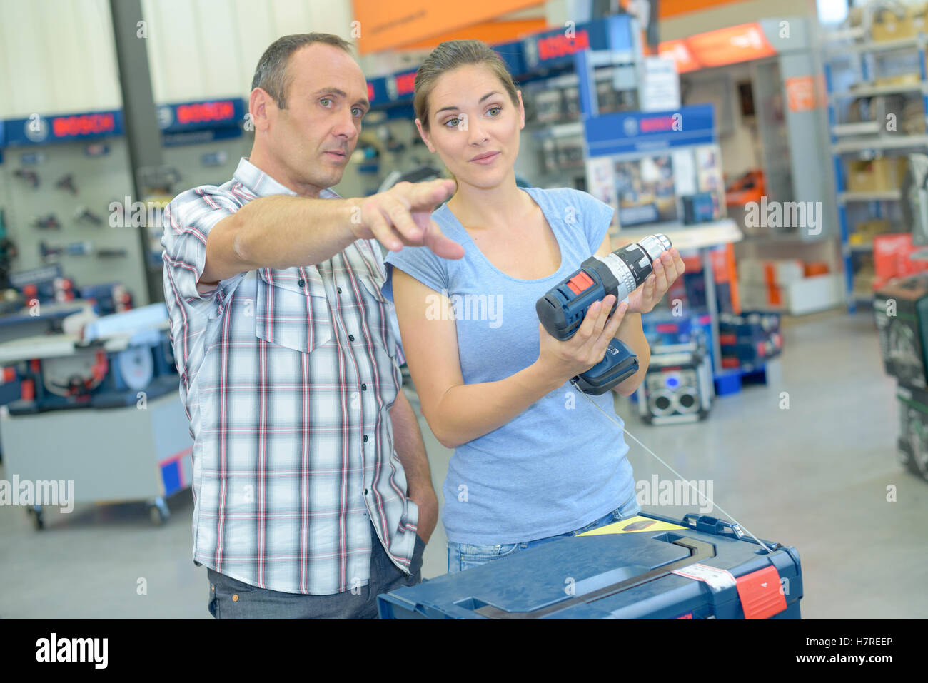Couple in hardware shop, man pointing - Stock Image