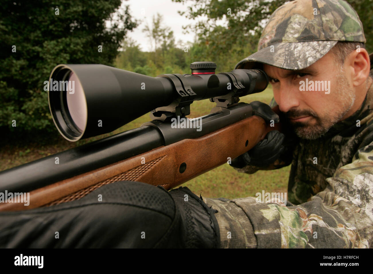 hunter ground hunting whitetail deer with scoped rifle stock photo
