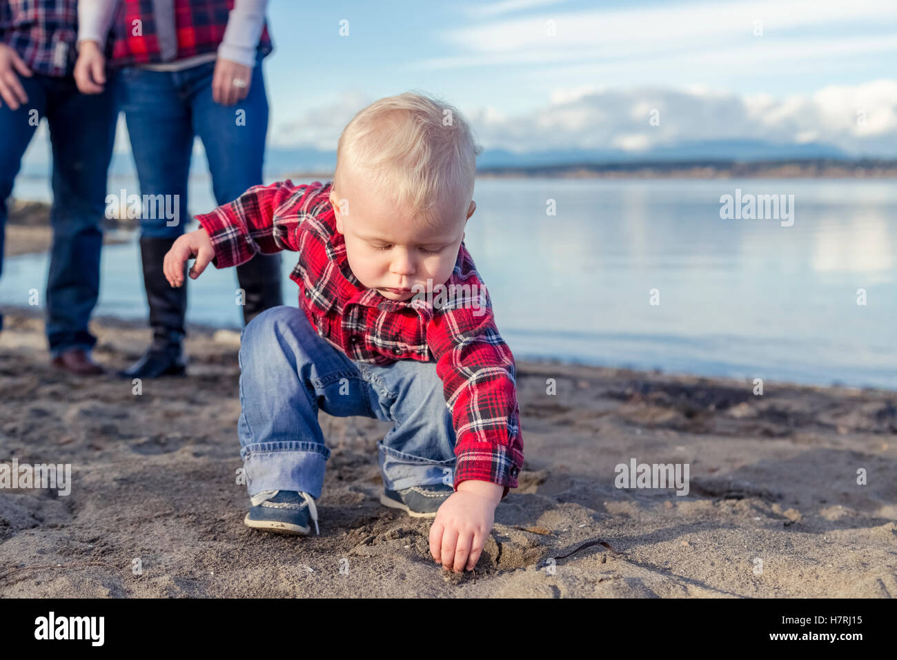 A young toddler gets his hands dirty playing with sand on the beach while his parents look on from the background; - Stock Image
