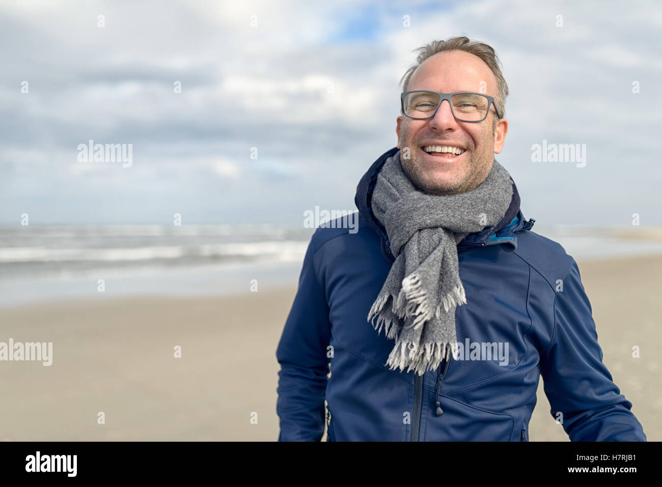 Happy laughing middle-aged man wearing glasses and a knitted woollen scarf standing on a deserted autumn beach on - Stock Image