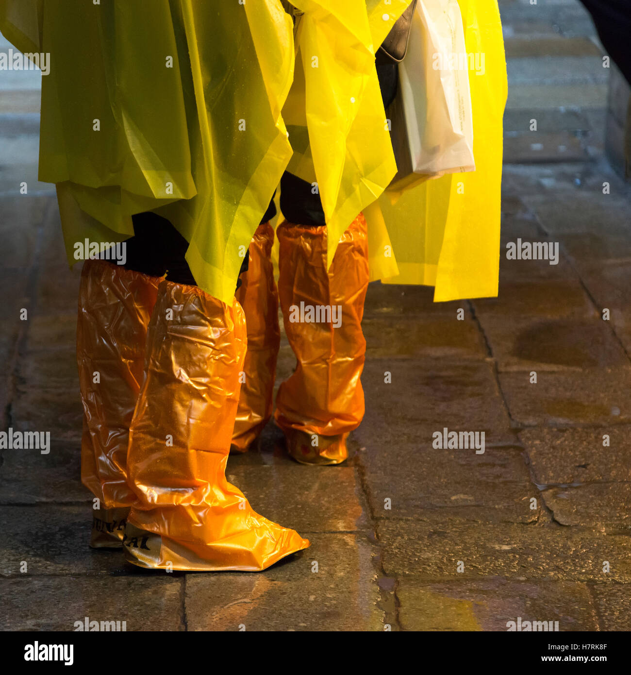 People standing with yellow rain ponchos and footwear covered in orange plastic covers; Venice, Italy - Stock Image