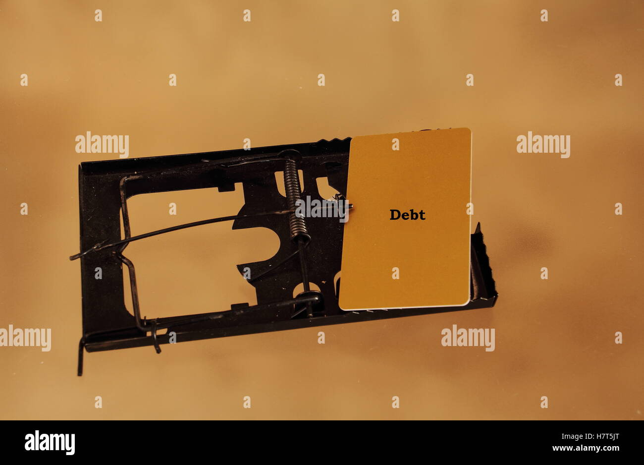 A credit card snared in a rat trap concept the debt trap image with copy space - Stock Image