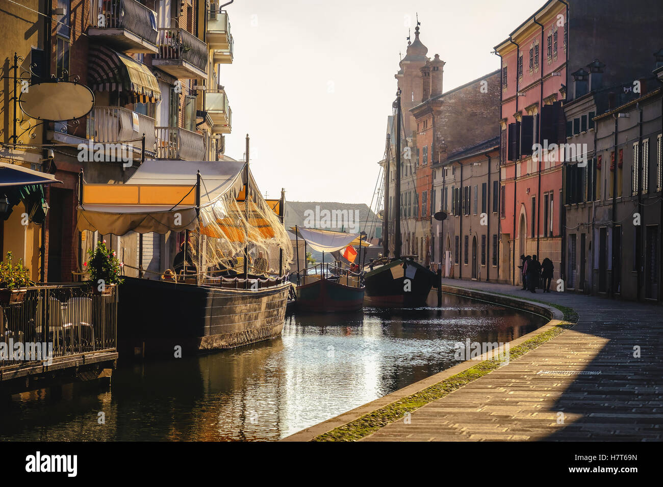 venice village sunset romantic haze shadow boat restaurant warm tone canal - Stock Image