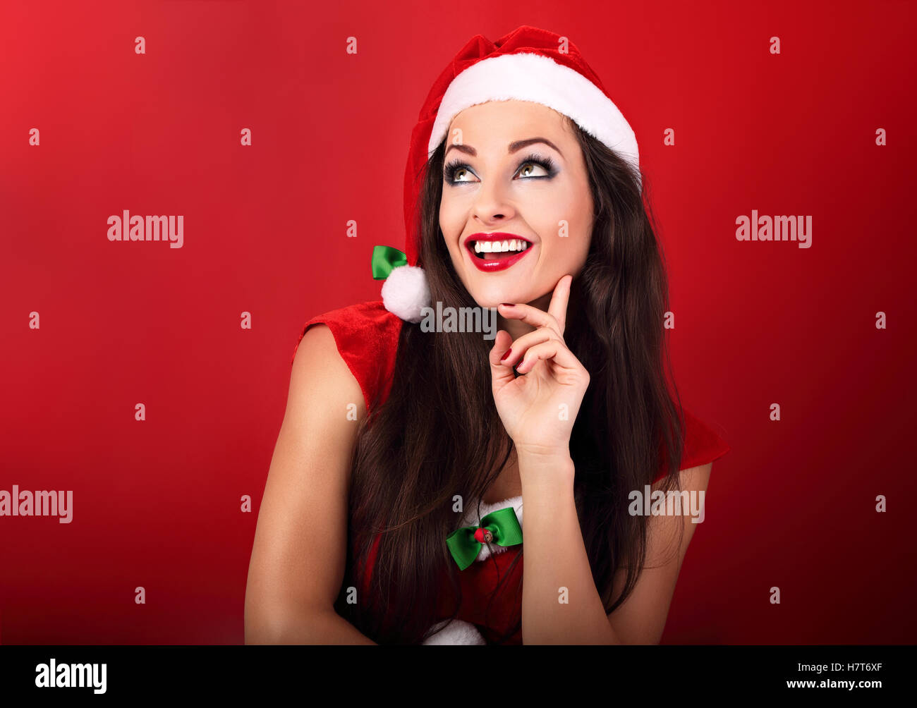 f9ce6a00beb65 Happy excited happy woman in santa claus christmas costume looking up on  red background with empty copy space.