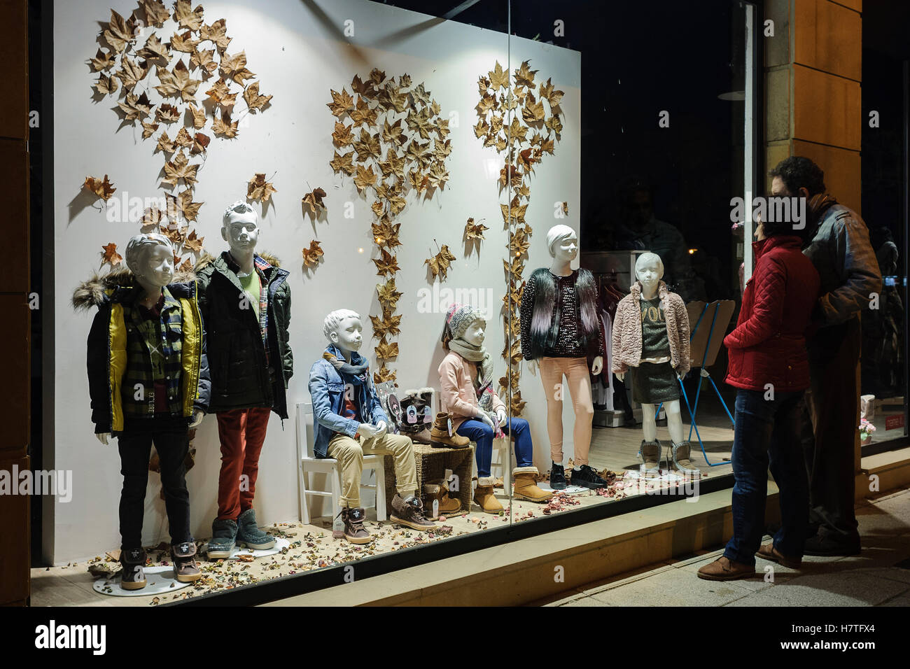 Sale of winter clothes for young children, in a showcase of the town of Colindres, Cantabria, Spain, Europe. - Stock Image