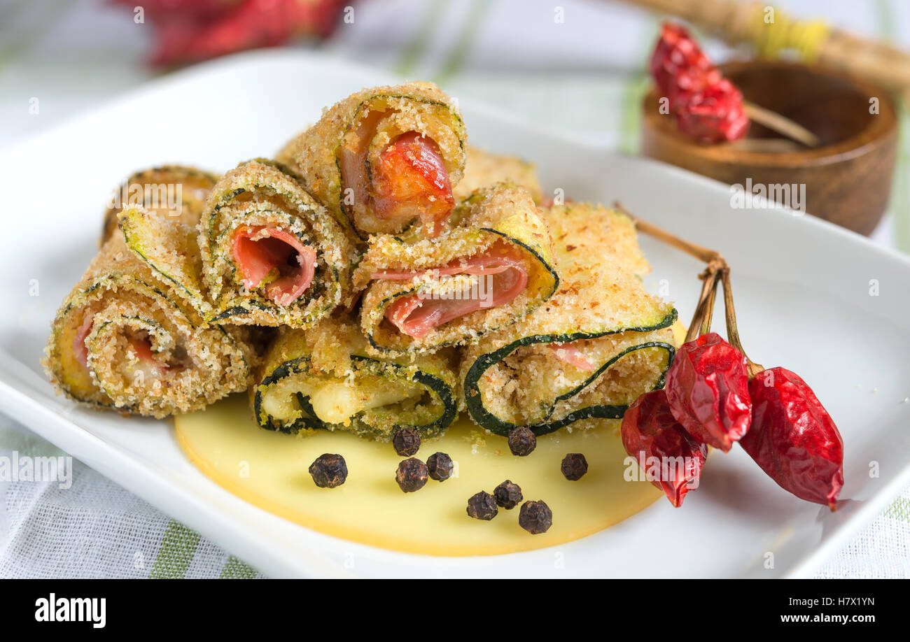 gratinated zucchini rolls with cheese, bacon and breadcrumbs - Stock Image