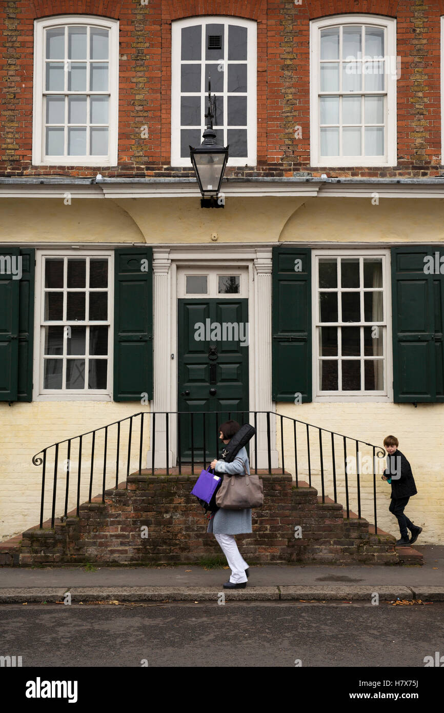 UK, England, Buckinghamshire, West Wycombe, High Street, mother and son passing Steps House, the former Manor House Stock Photo