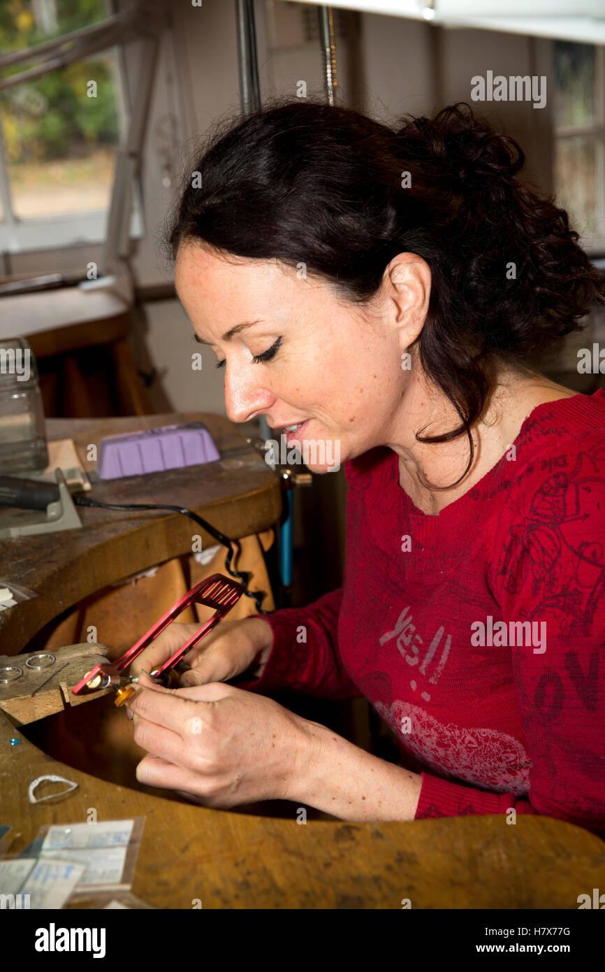 UK, England, Buckinghamshire, West Wycombe, High Street, artisan silversmith Justine Holliday at work making jewellery - Stock Image