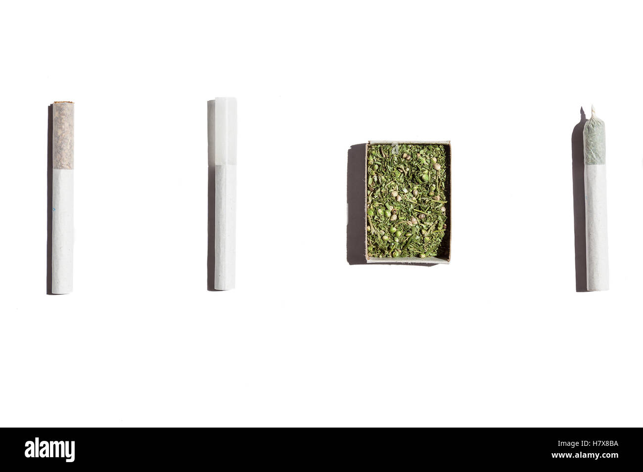 Cigarettes with weed.Open box with hemp, one empty cigarette and two filled with tobacco and cannabis isolated on - Stock Image