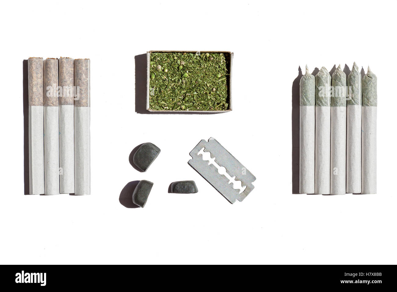 Cannabis in box.Four rolled cigarettes with tobacco, five with hemp, box with cannabis , blade and stones lay on - Stock Image