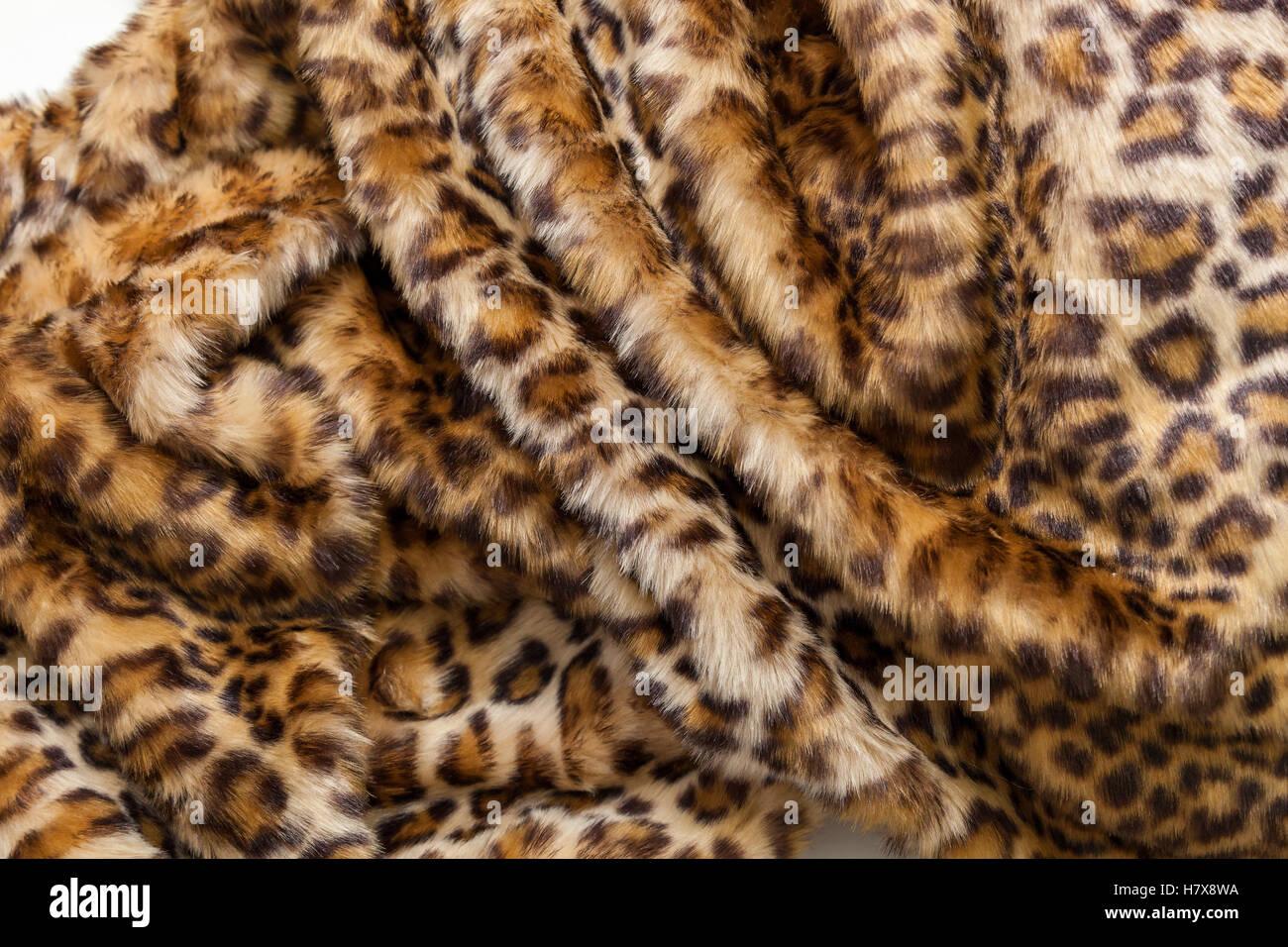 Leopard fur textile. The folds of the leopard fur textile close up. - Stock Image