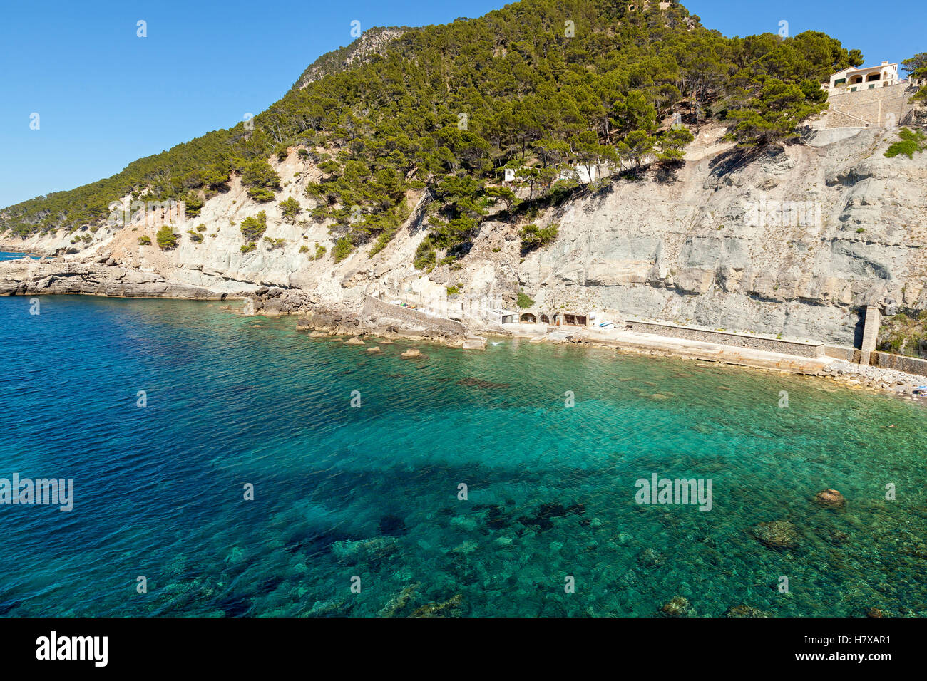 Azure Bay. Azure bay with crystal clear water through which can be seen the rocky bottom On top of the mountain - Stock Image