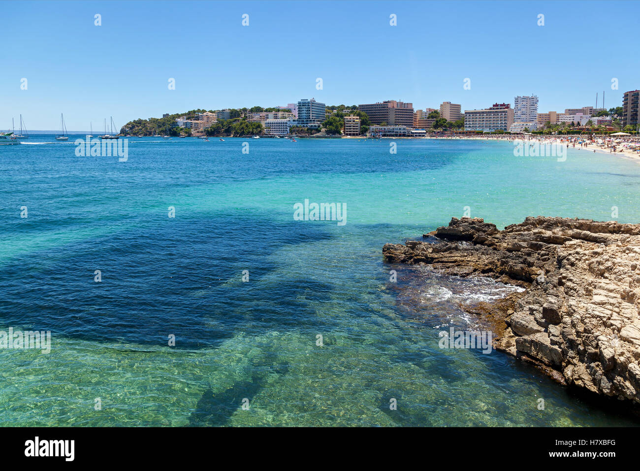 Rocky shore of Palmanova. Rocky shore of Palmanova on a sunny day. In the distance the crowded beach, as well as - Stock Image