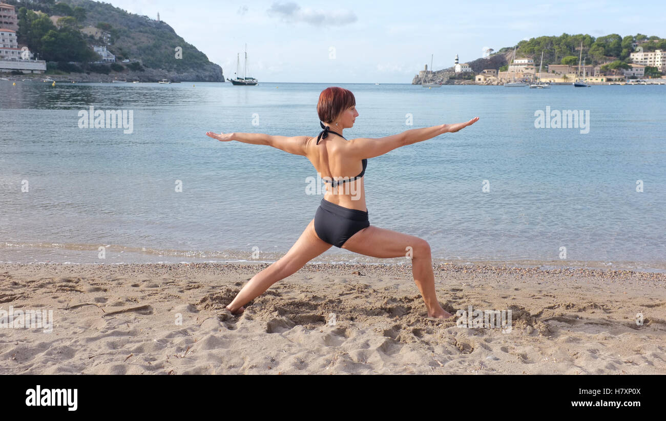 A woman practicing yoga on a beach in Majorca. Warrior pose shown. - Stock Image