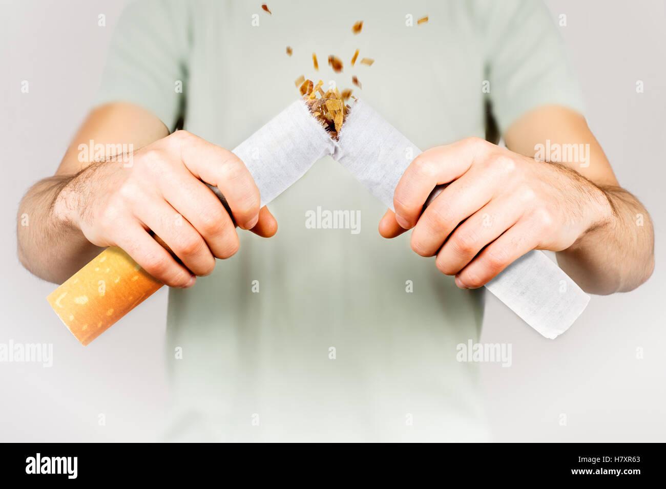 Quit smoking - male smoker breaking giant cigarette - Stock Image