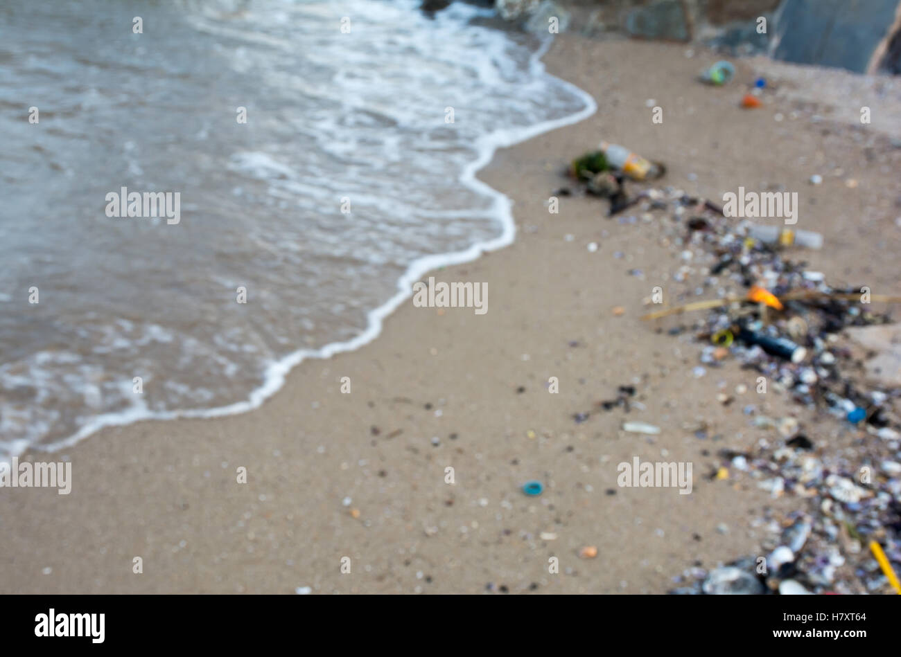 Pollution on the beach with blurred background - Stock Image