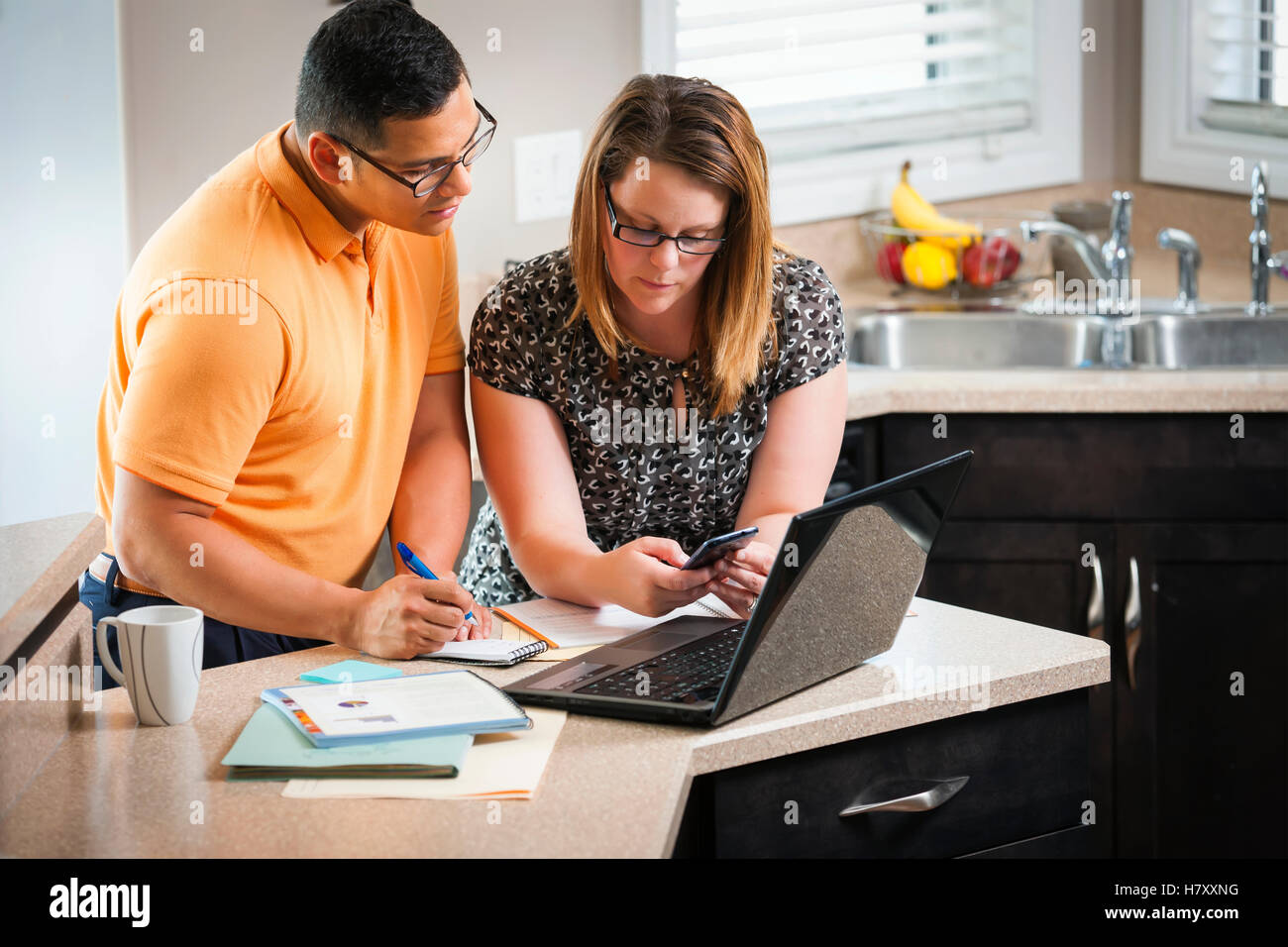 A man and woman standing in the kitchen working together with a calculator and computer; Regina, Saskatchewan, Canada - Stock Image