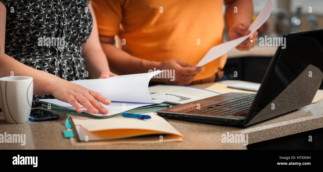 A man and woman standing in the kitchen working together with documents and a computer; Regina, Saskatchewan, Canada - Stock Image