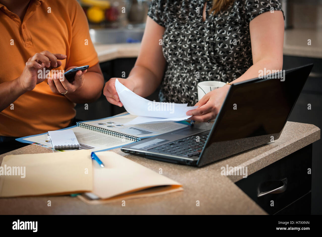 A man and woman in the kitchen working together with documents and a computer; Regina, Saskatchewan, Canada - Stock Image