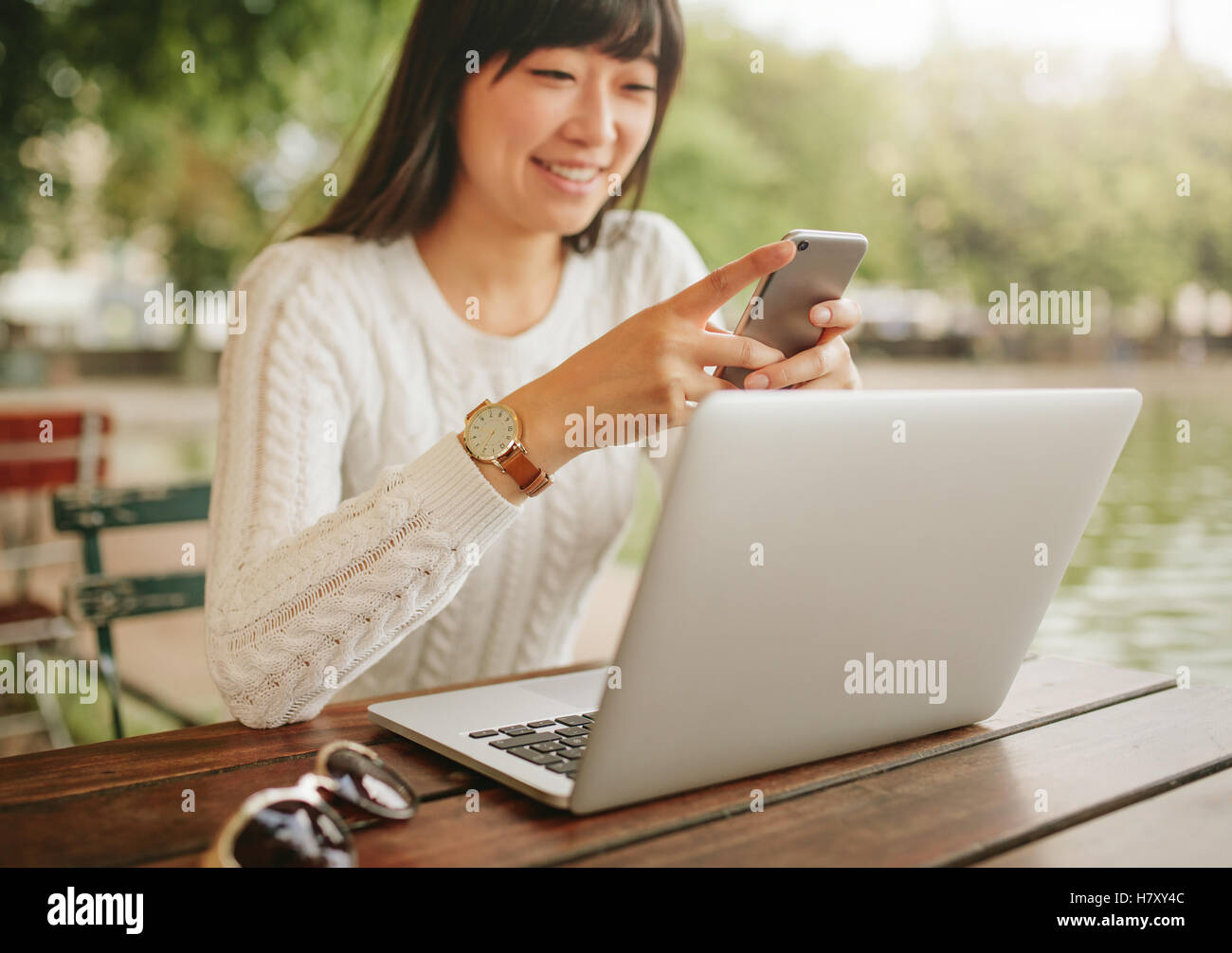 Shot of happy asian woman using smartphone at outdoor coffee shop. Female sitting at cafe table with laptop outdoors - Stock Image