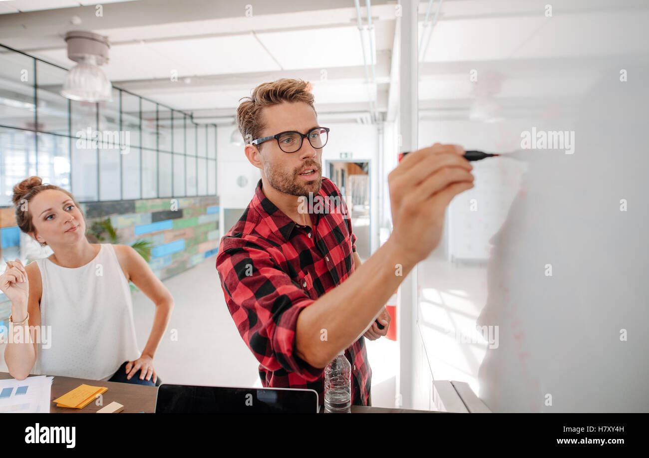 Casual business giving a presentation to coworkers. Startup meeting in conference room, businesspeople discussing - Stock Image