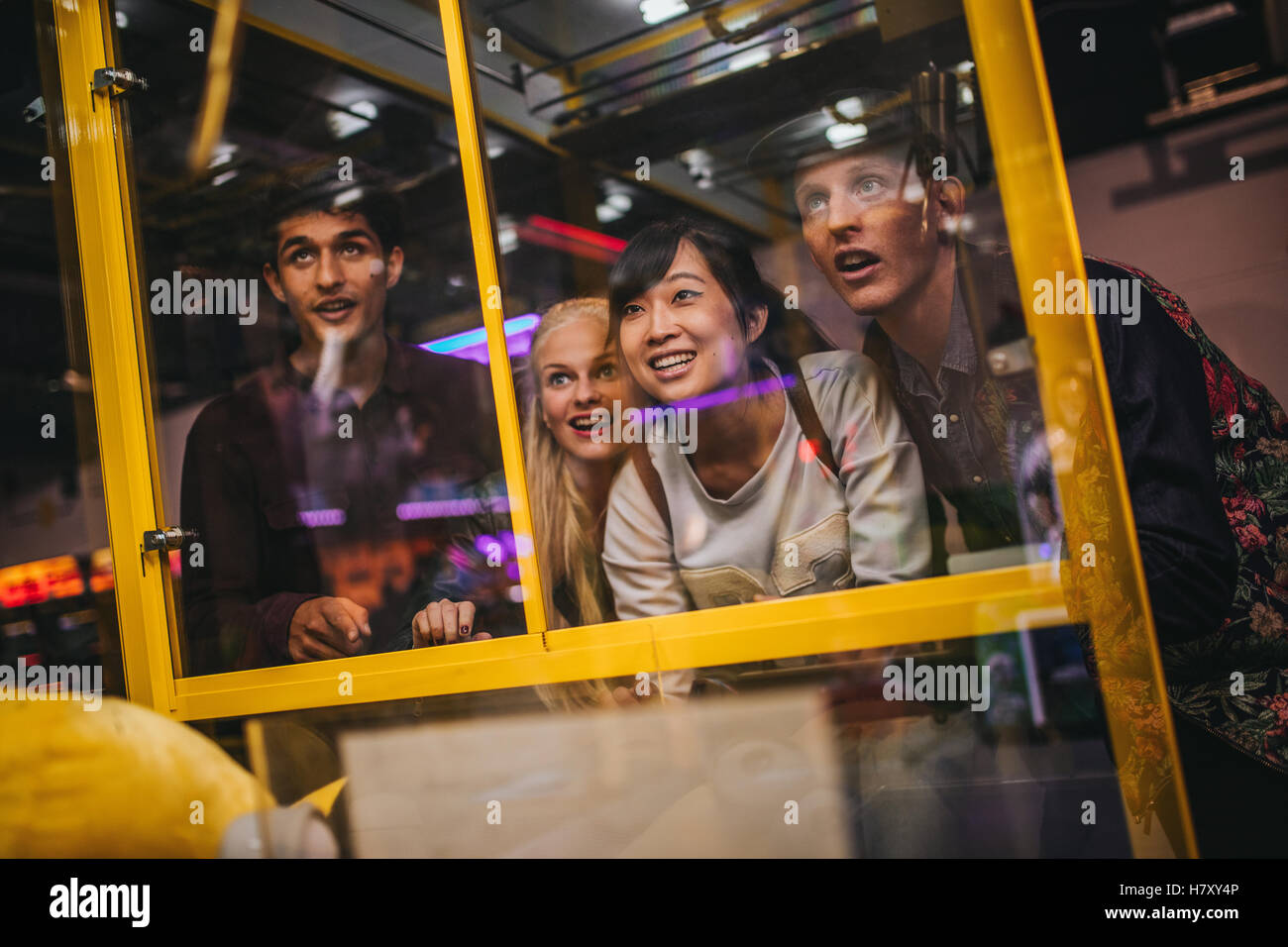 Cheerful young friends playing toy grabbing game at amusement park. Happy woman selecting a random soft toy in a - Stock Image