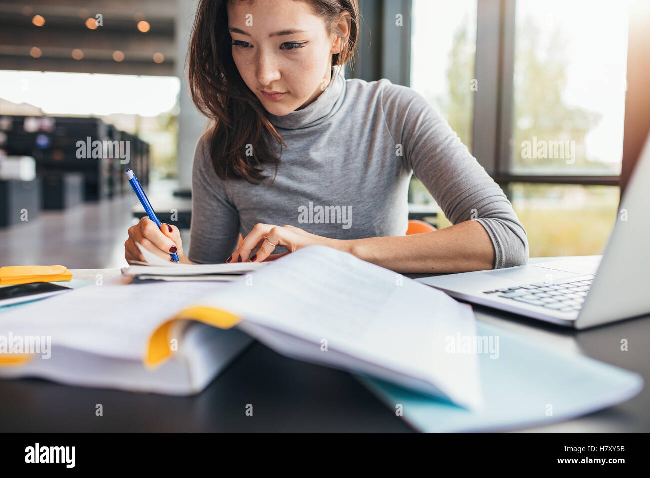 Close up image of a young female student doing assignments in library. Asian woman taking notes from textbook. - Stock Image