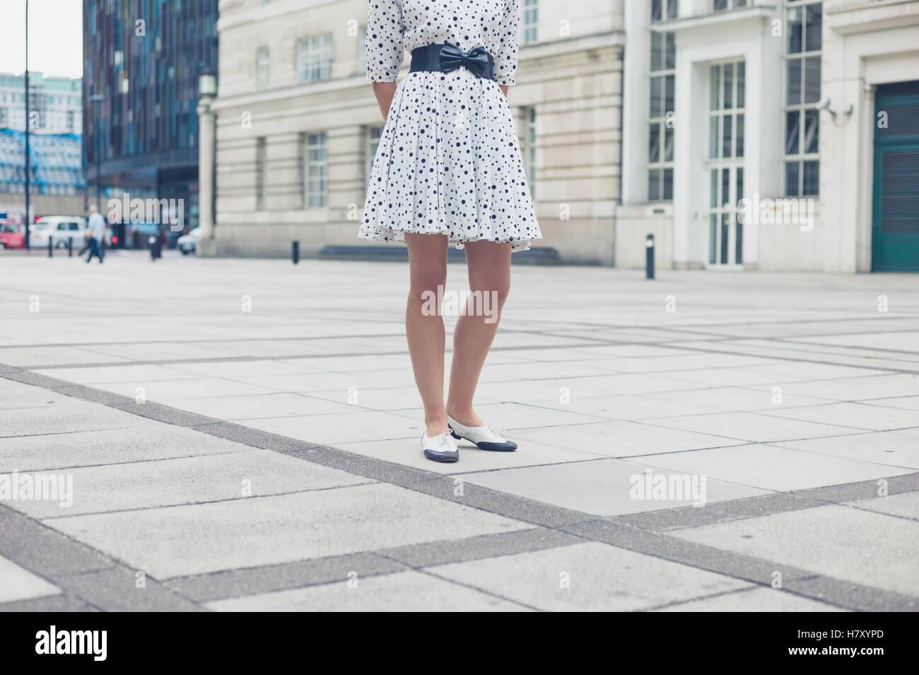 b983b22baca A young woman wearing a white dress with black dots is standing in a square  in