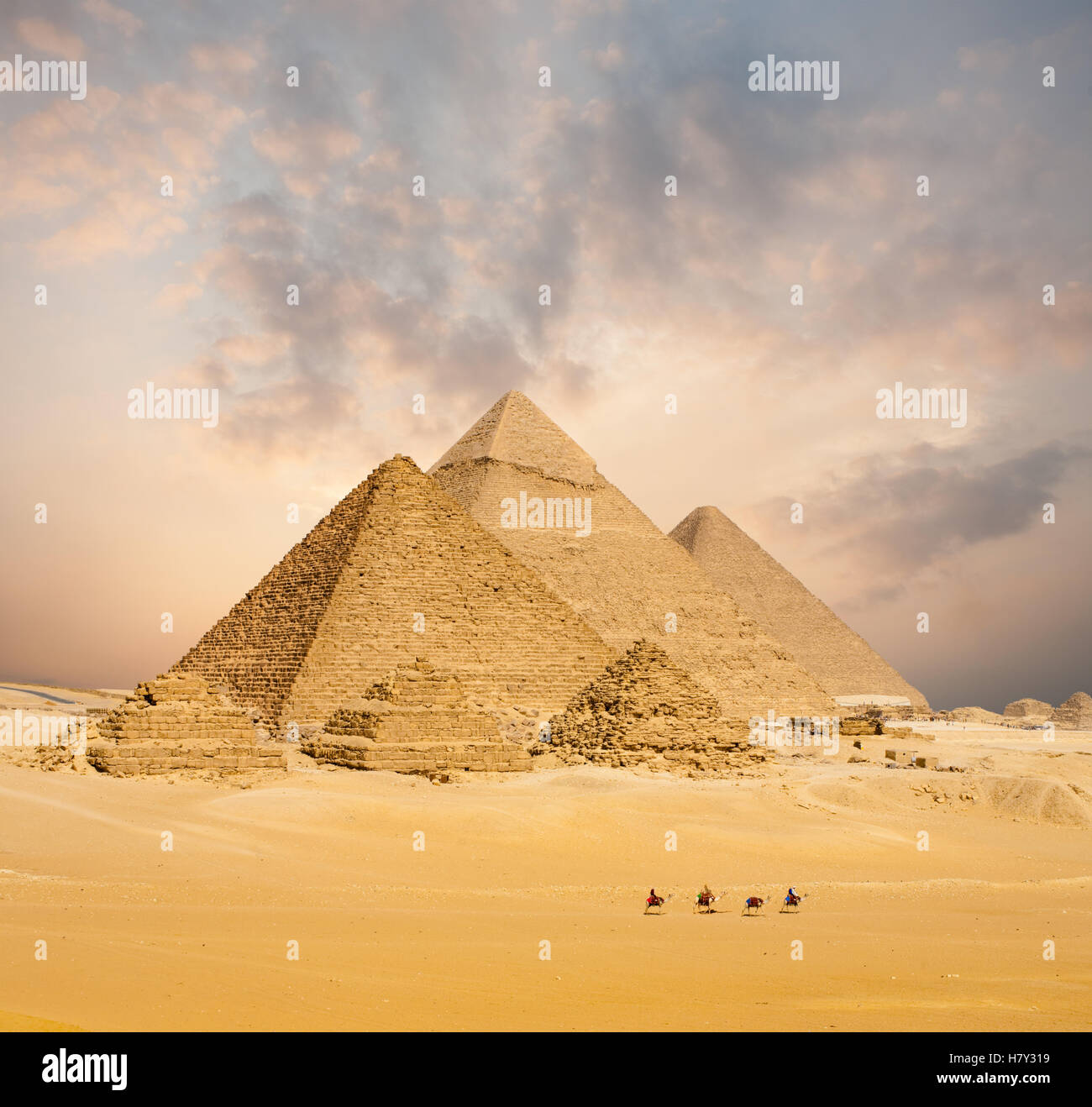 Dramatic sunset behind all distant Egyptian Pyramids together with line of camels walking in foreground in Giza, - Stock Image
