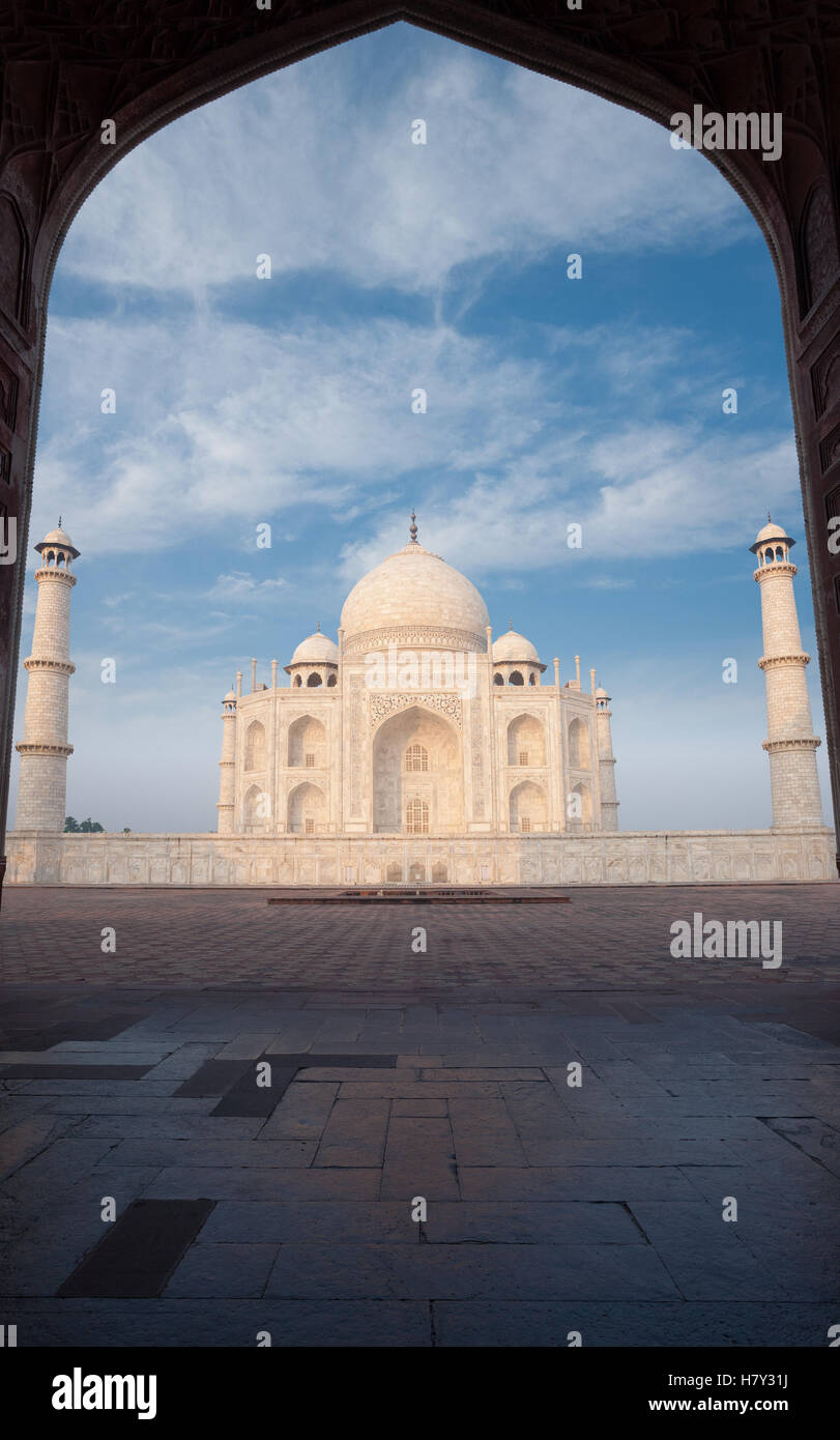 White marble of Taj Mahal framed through the silhouette of east jawab large door with nobody present on a blue sky - Stock Image