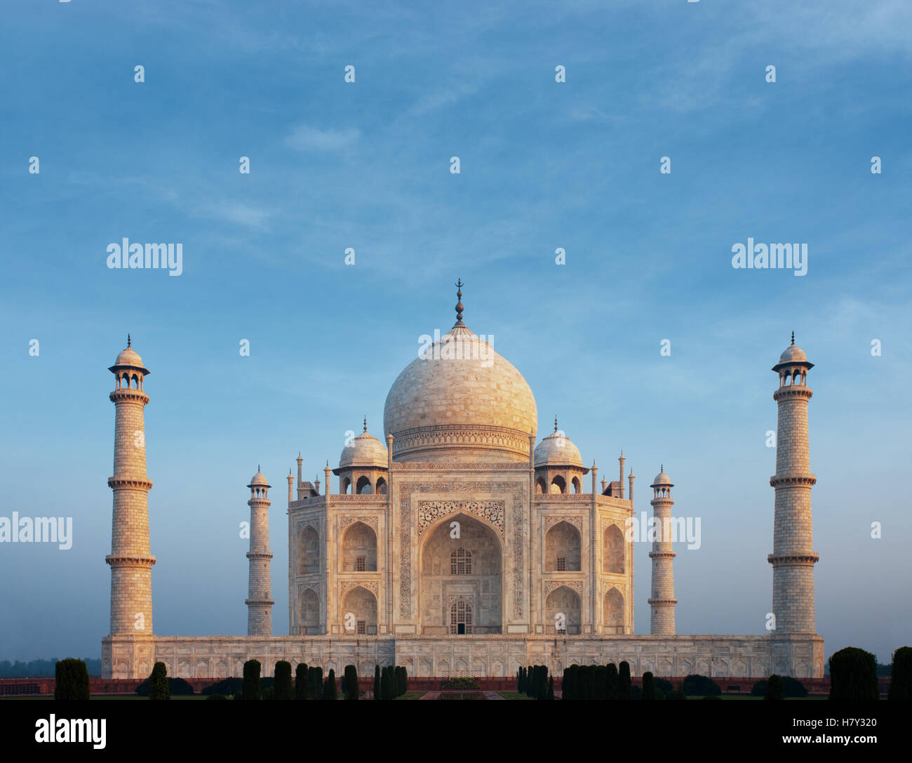 A beautiful morning orange glow on front marble facade of the iconic Taj Mahal centered under a calm morning blue sky from telep Stock Photo