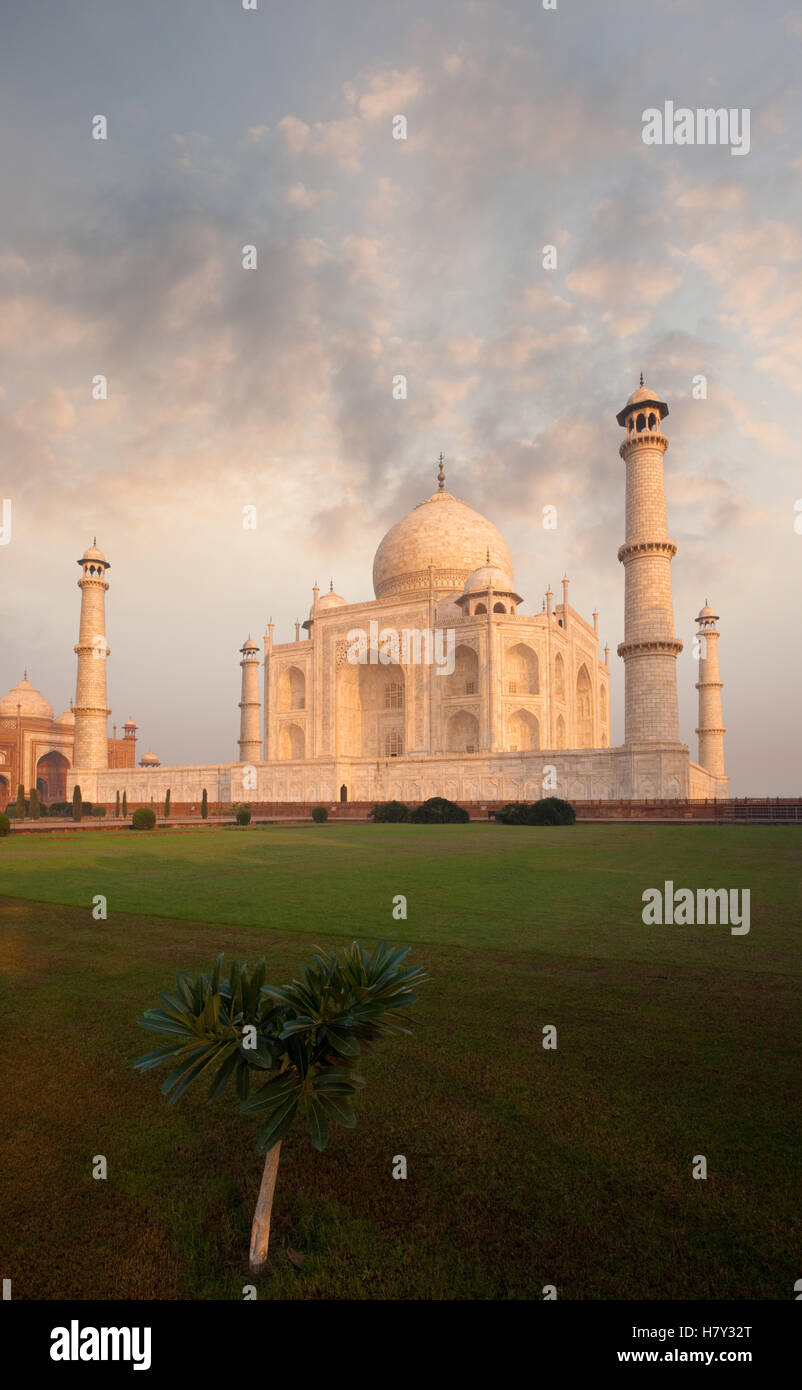 Fiery sky behind iconic orange glowing marble of Taj Mahal and front lawn foreground with nobody present in Agra, - Stock Image