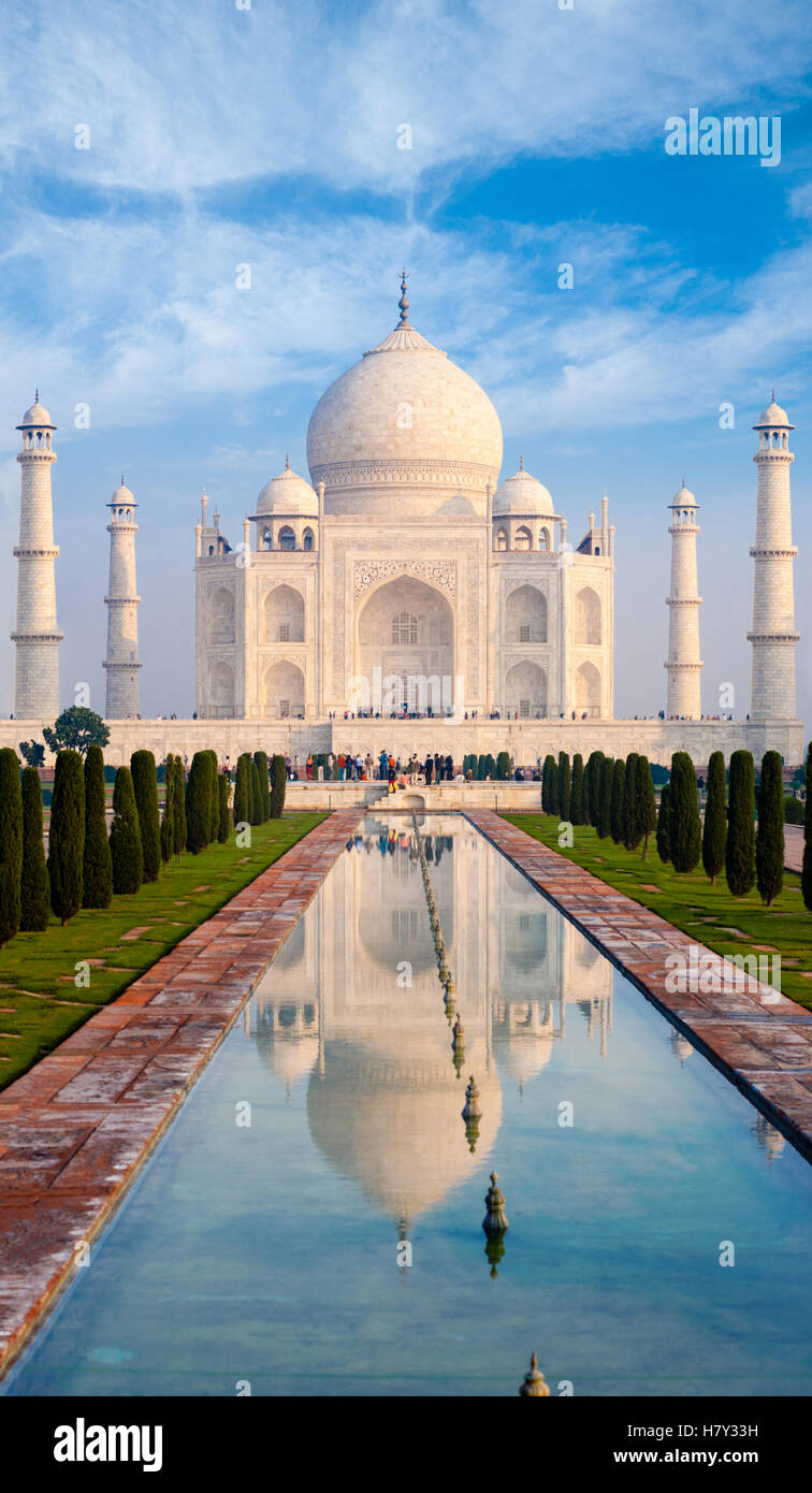 Distant telephoto front centered view of Taj Mahal and compressed long water fountain in foreground on clear blue - Stock Image