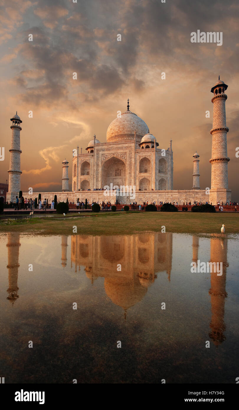 Iconic Taj Mahal and colorful sunset sky reflected in a puddle of water on front lawn in evening at Agra, Uttar - Stock Image