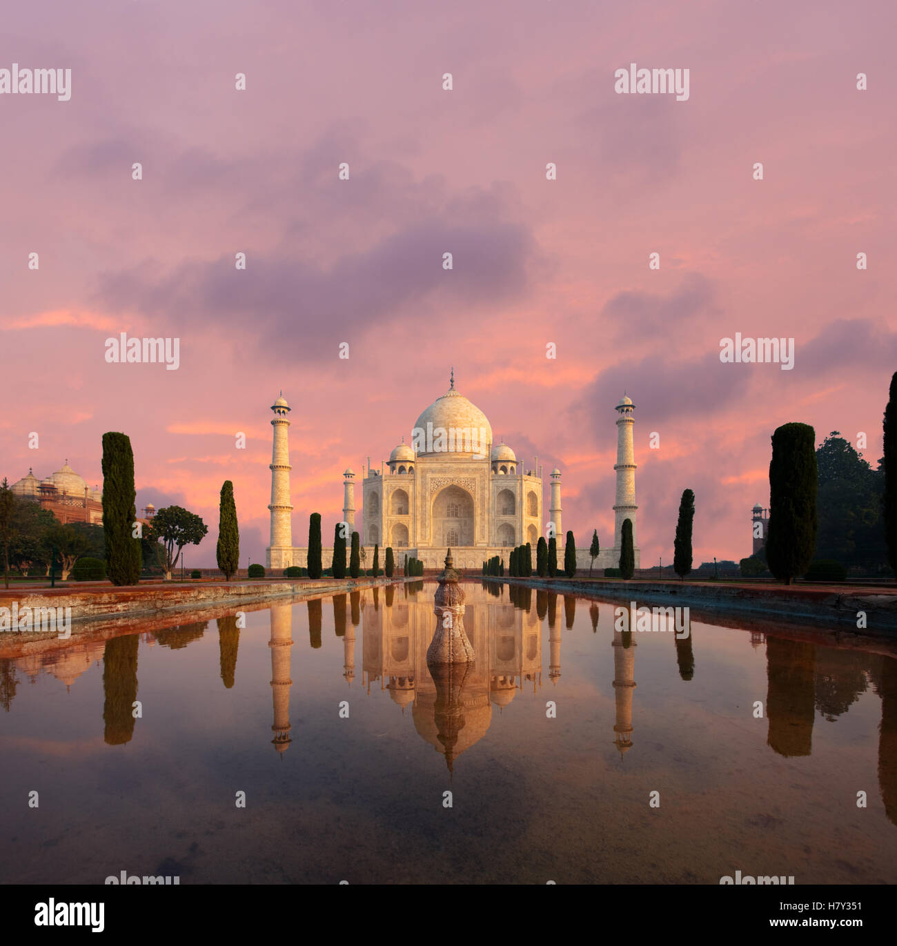 Nobody present as Taj Mahal glows beautifully at sunset reflected in front garden water fountain pool of water under - Stock Image