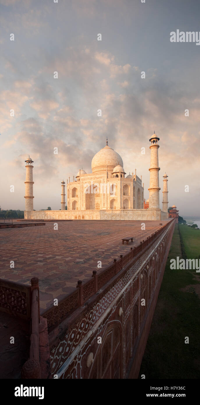 Red sandstone base of the rear of Taj Mahal rises out of the bank of the Jamuna river at sunrise in Agra, India. - Stock Image