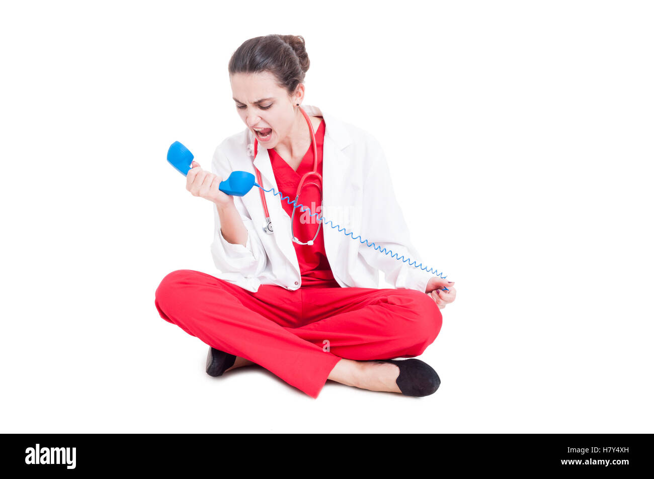 Angry medic woman screaming on telephone receiver as conflict concept isolated on white - Stock Image