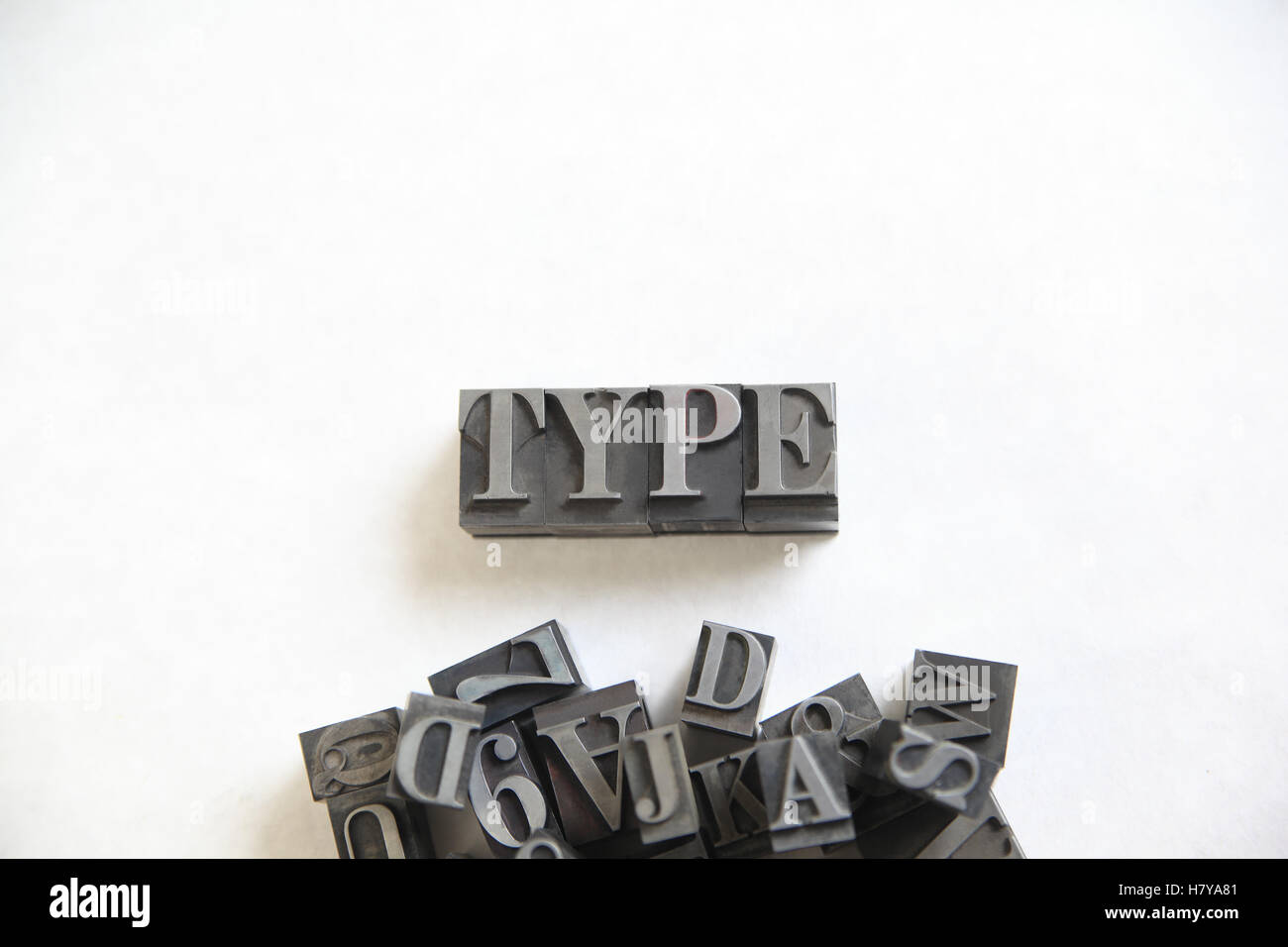 The word type in metal letters with a pile of assorted letters and numbers underneath - Stock Image