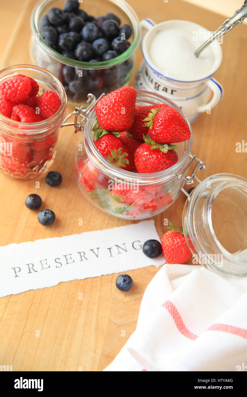 Strawberries, raspberries and blueberries in glass jars with the word preserving on cutting board - Stock Image