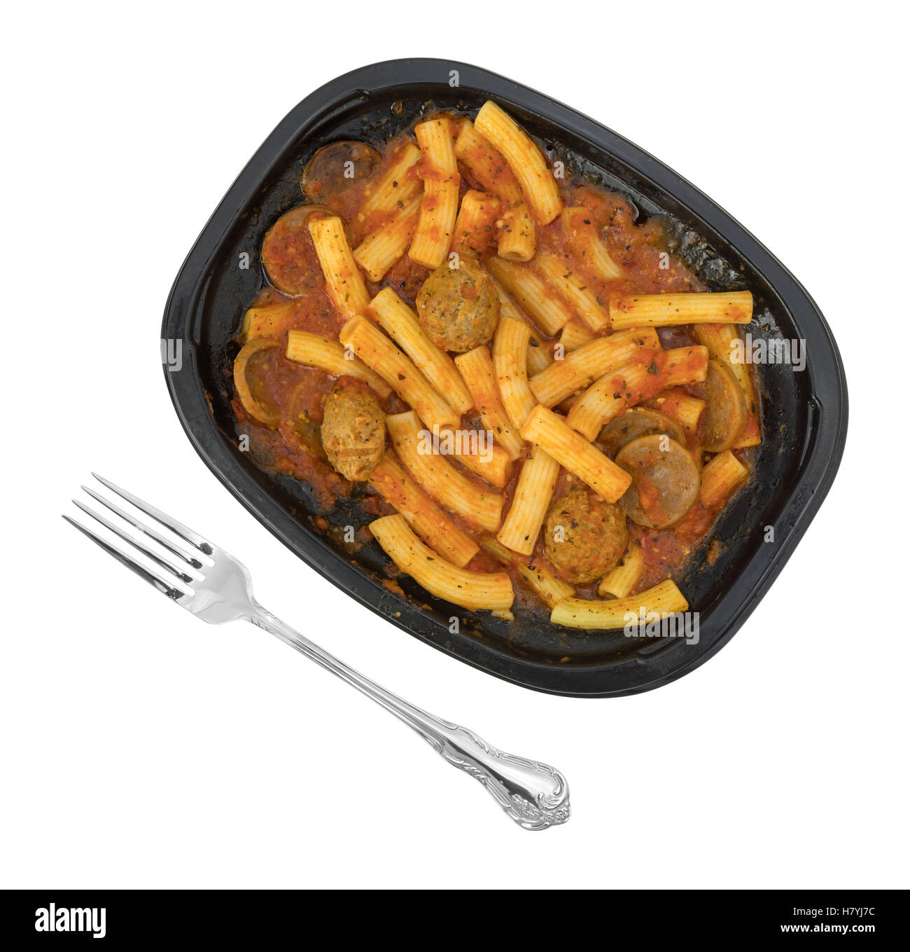 A TV dinner of rigatoni pasta with sausage and meatballs in a marinara sauce in a black tray with a fork to the - Stock Image
