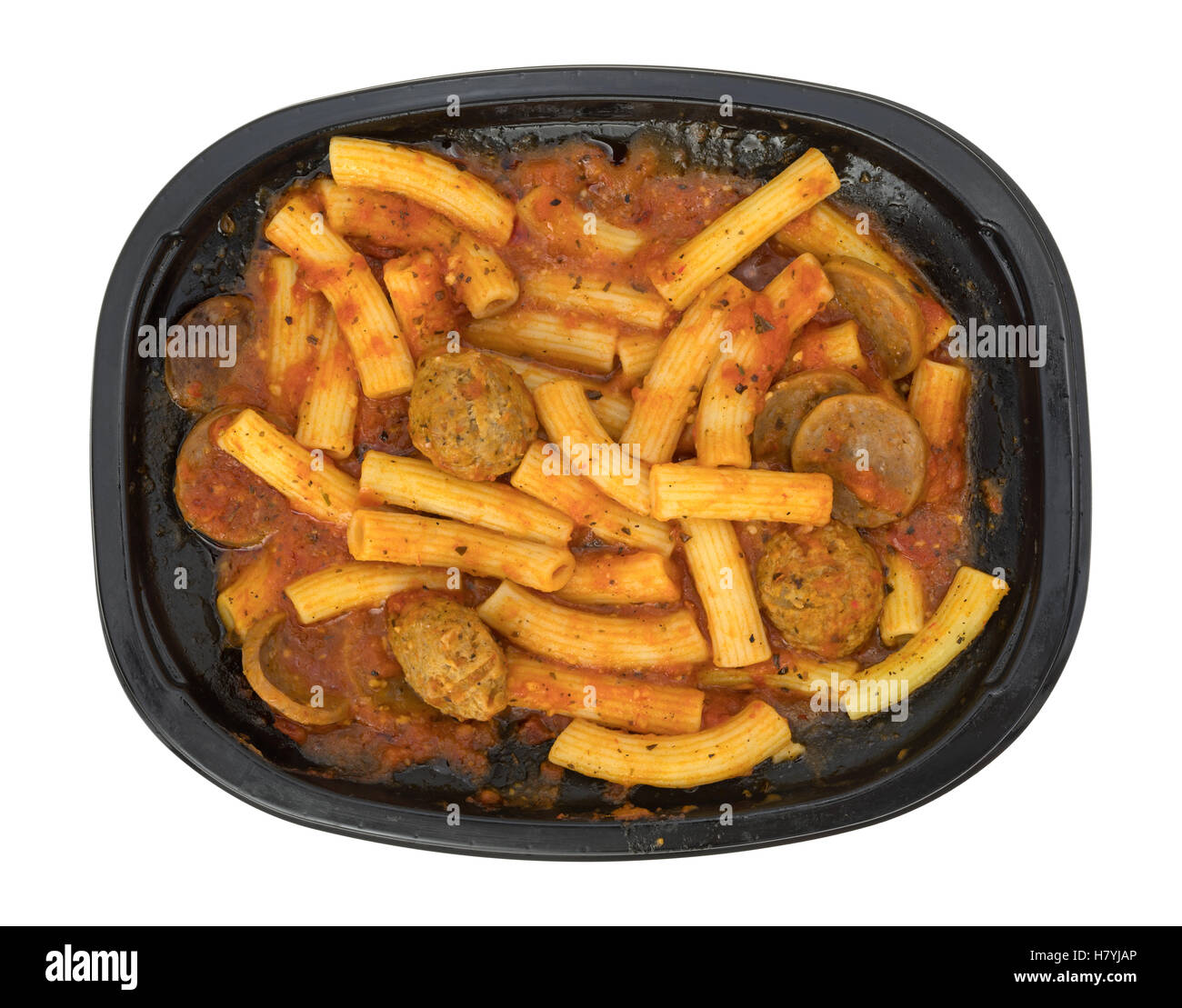 A TV dinner of rigatoni pasta with sausage and meatballs in a marinara sauce in a black tray isolated on a white - Stock Image
