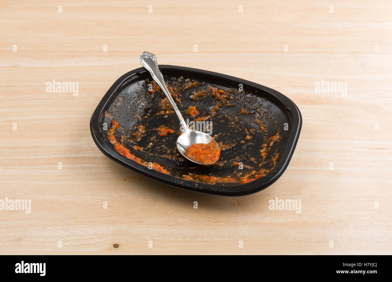 A spoon with a tomato and cheese sauce on a finished black TV dinner tray atop a wood table. - Stock Image