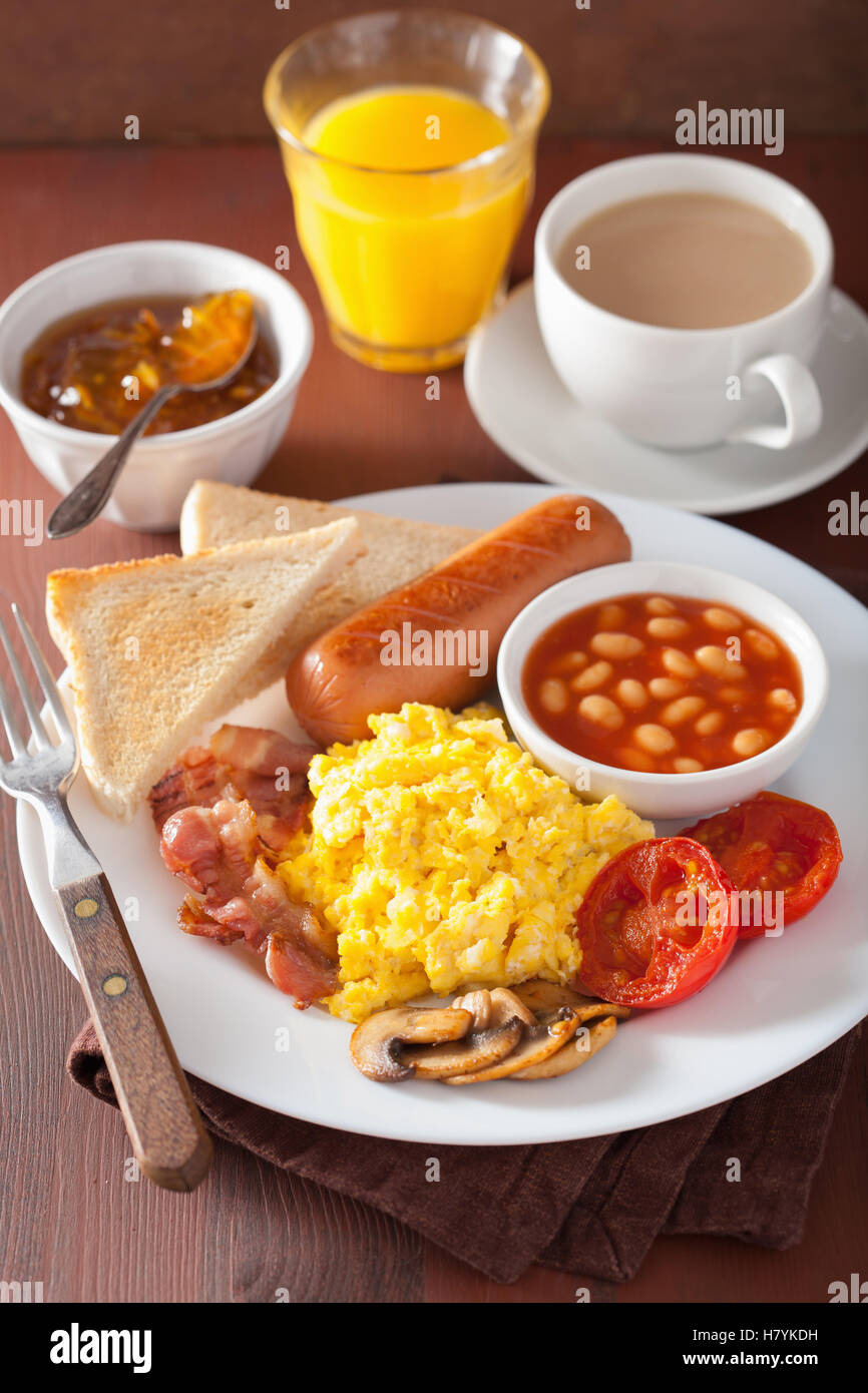 full english breakfast with scrambled eggs, bacon, sausage, beans, tomato - Stock Image