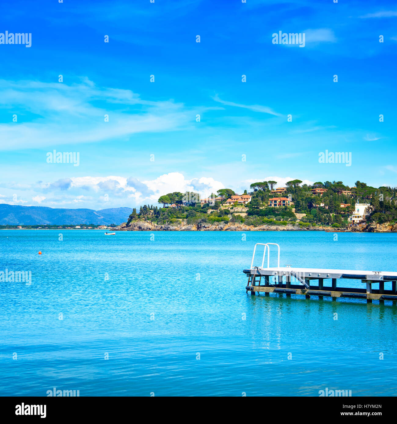 Wooden pier or jetty on a blue sea and clear sky. Bay beach in Monte Argentario, Porto Santo Stefano, Tuscany, Italy - Stock Image