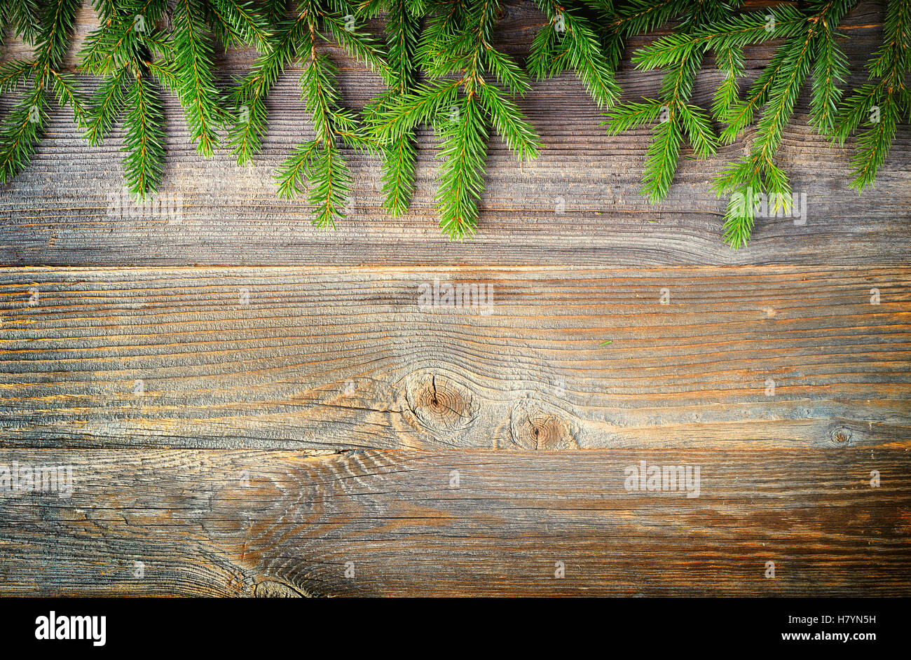 Christmas fir tree or spruce branches on wooden background, top view - Stock Image