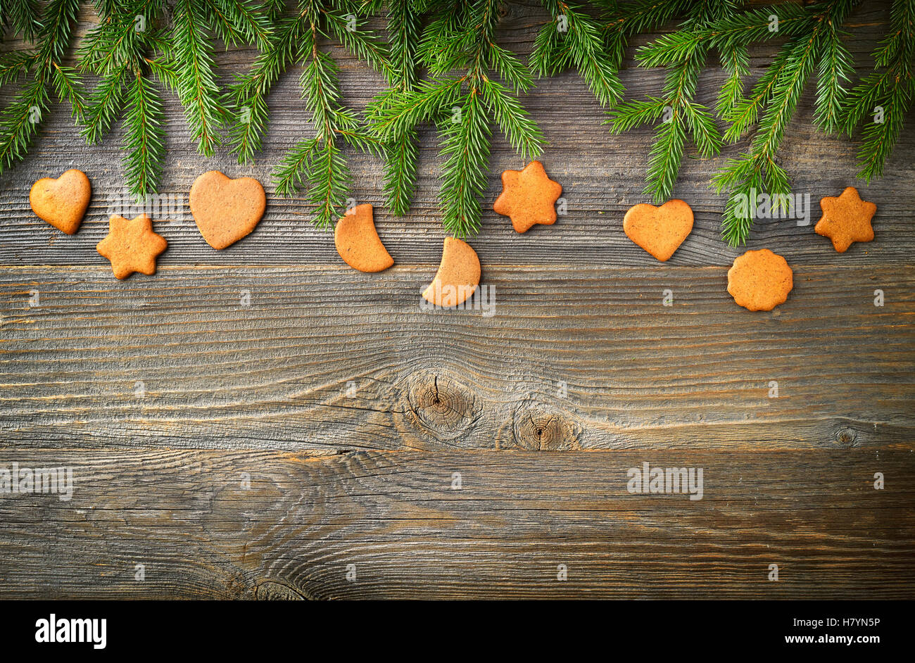 Christmas fir tree or spruce branches and christmas cookies on wooden background, top view - Stock Image