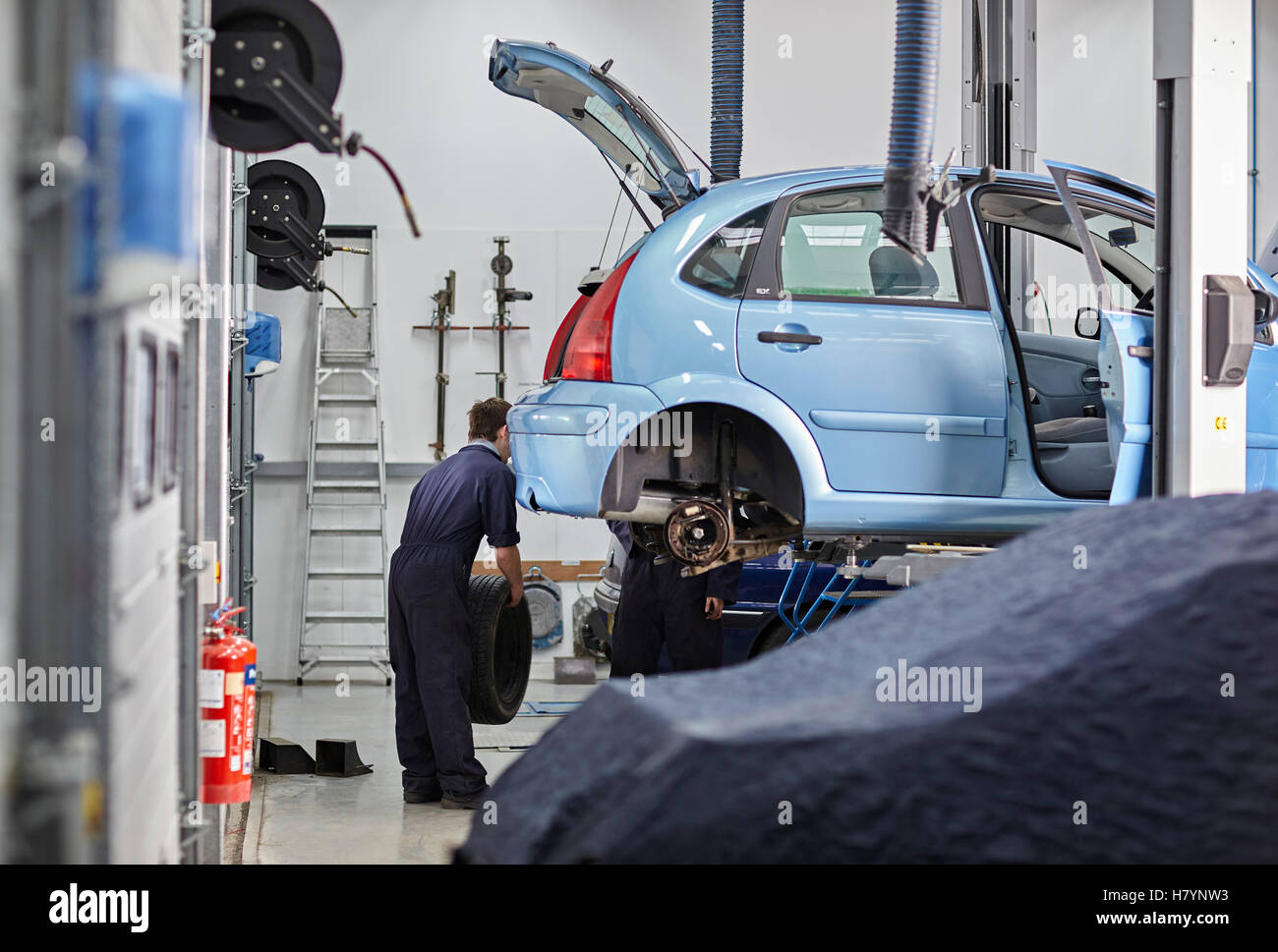 Mechanic Servicing Wheel Change Tyre MOT Motor Vehicle Car repair - Stock Image