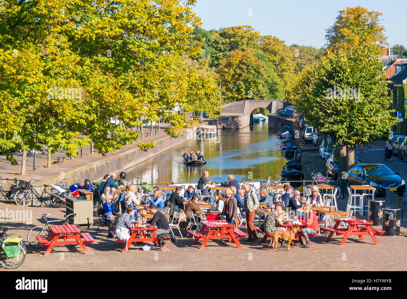 People on waterfront outdoor terrace of cafe and tourboat on canal in Naarden-Vesting, North Holland, Netherlands - Stock Image